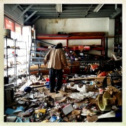 John, a former diplomatic courier, searches through a destroyed pet store for food for feral cats on Staten Island.
